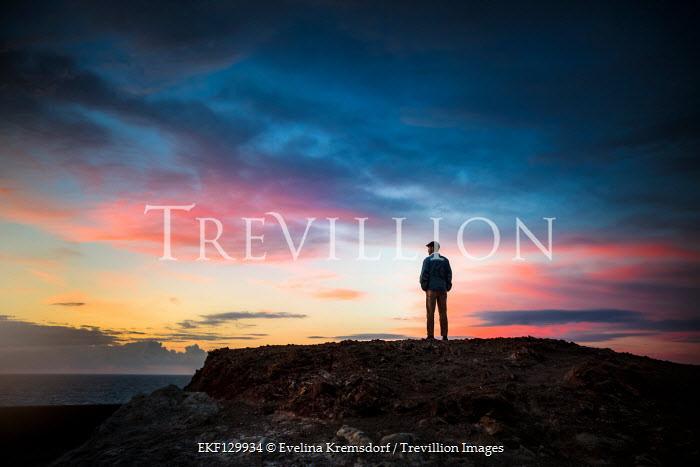 Evelina Kremsdorf MAN STANDING ON CLIFF WATCHING SEA AT SUNSET Men