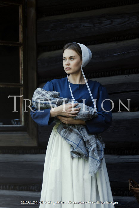 Magdalena Russocka amish woman holding infant baby by log cabin