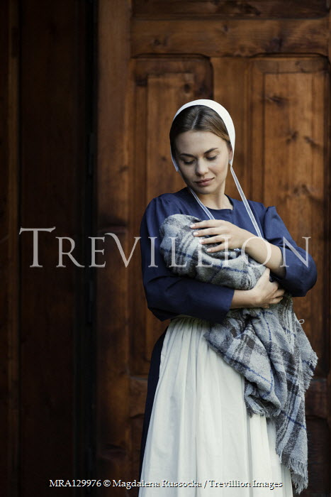 Magdalena Russocka amish woman holding infant baby by wooden door