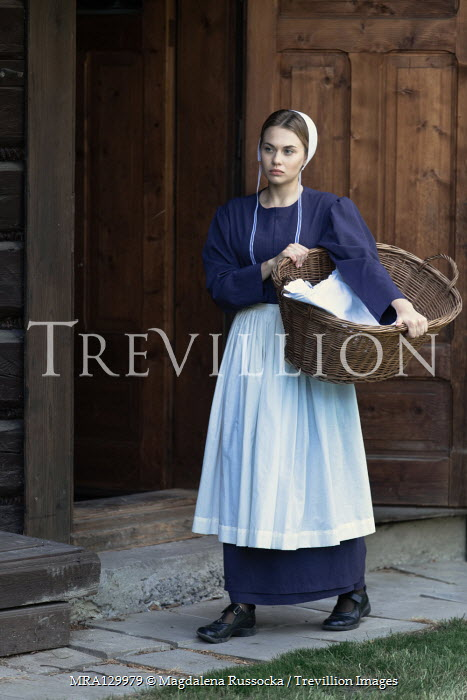 Magdalena Russocka amish woman carrying laundry basket by log cabin