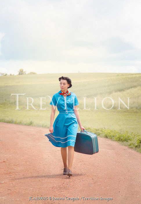 Joanna Czogala WOMAN WALKING ON COUNTRY ROAD CARRYING SUITCASE Women