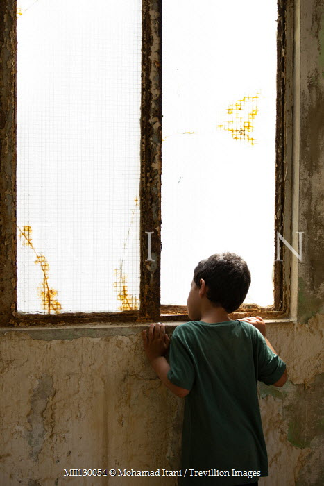 Mohamad Itani LITTLE BOY IN DERELICT BUILDING WATCHING AT WINDOW Children