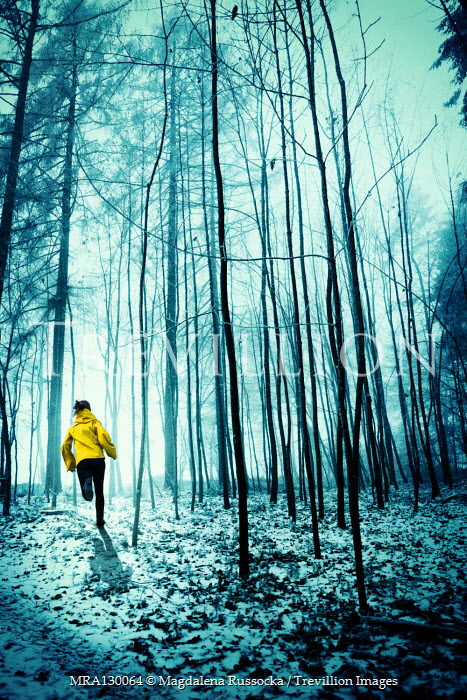 Magdalena Russocka modern woman in yellow jacket running in snowy woods
