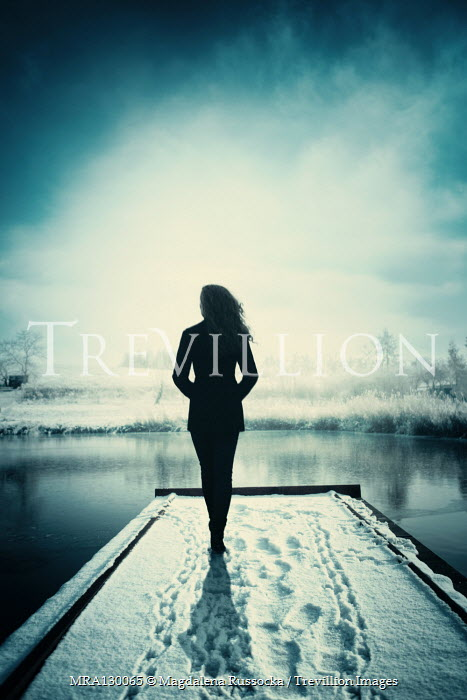 Magdalena Russocka silhouette of modern woman standing on snowy bridge lake