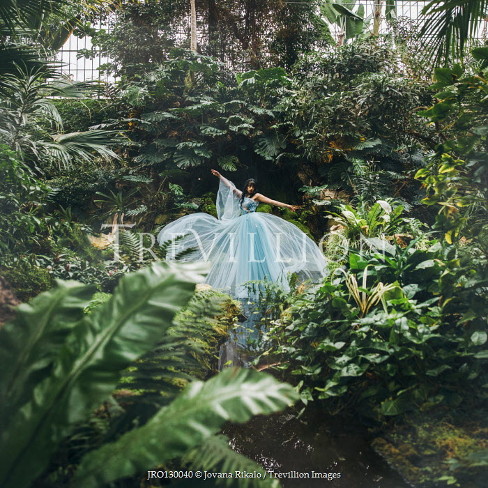 Jovana Rikalo WOMAN IN BALLGOWN IN GLASSHOUSE WITH PLANTS Women