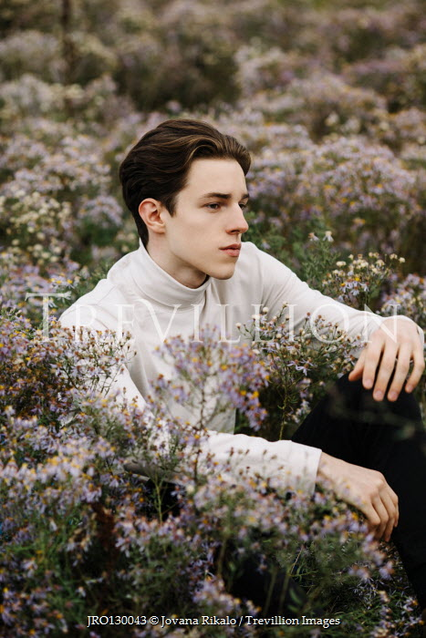 Jovana Rikalo YOUNG MAN SITTING IN MEADOW WITH FLOWERS Men