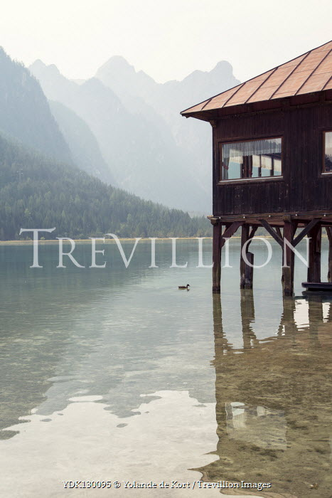 Yolande de Kort BUILDING ON STILTS IN LAKE WITH MOUNTAINS Miscellaneous Buildings
