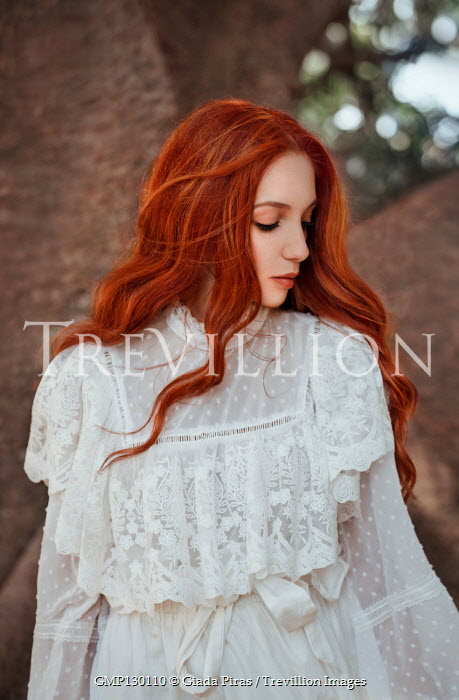 Giada Piras Young woman in white dress by tree trunk