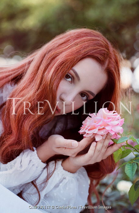 Giada Piras Young woman holding pink flower