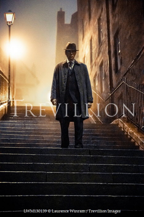 Laurence Winram Man in hat and coat standing on steps at night