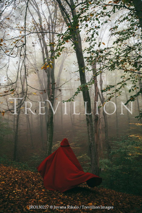 Jovana Rikalo Woman in red cloak walking in forest