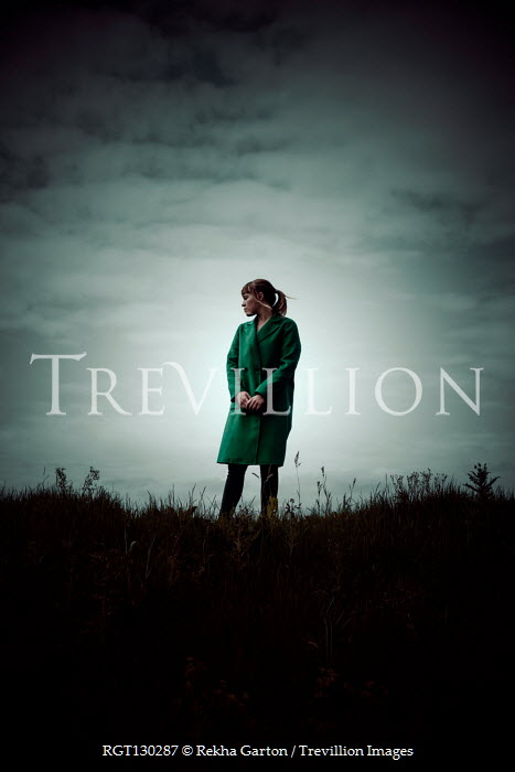 Rekha Garton Young woman in green coat standing on hill