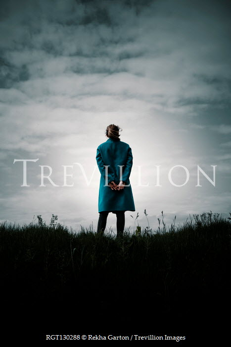Rekha Garton Young woman in blue coat standing on hill