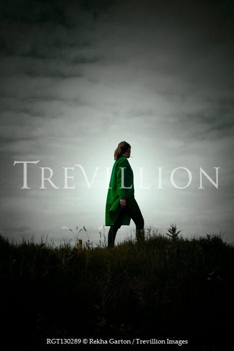 Rekha Garton Man in green coat walking on hill
