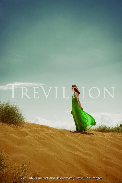 Svetlana Bekyarova Young woman in green dress standing on sand dunes