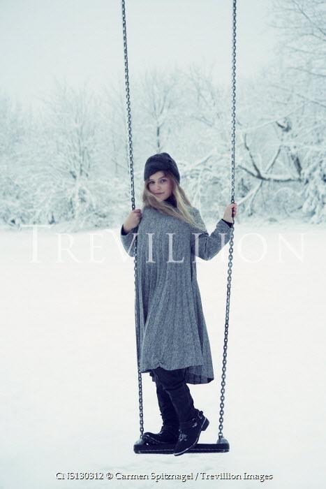 Carmen Spitznagel BLONDE GIRL STANDING ON SWING IN SNOWY GARDEN Women