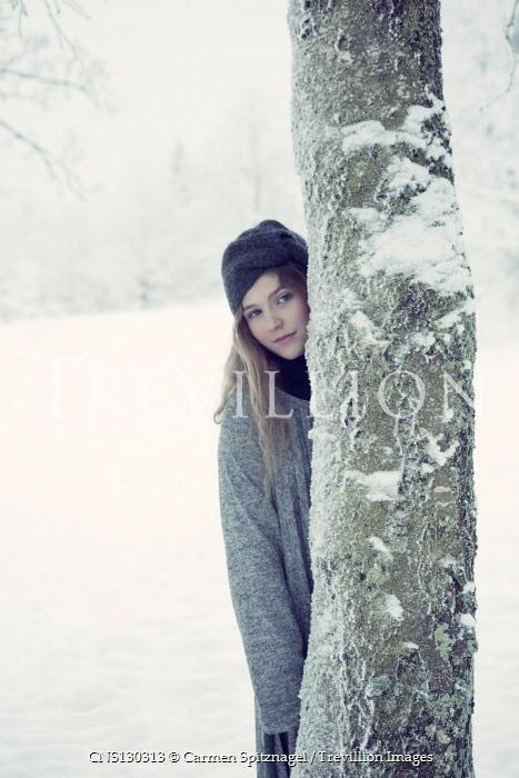 Carmen Spitznagel GIRL STANDING BEHIND TREE IN SNOWY COUNTRYSIDE Women