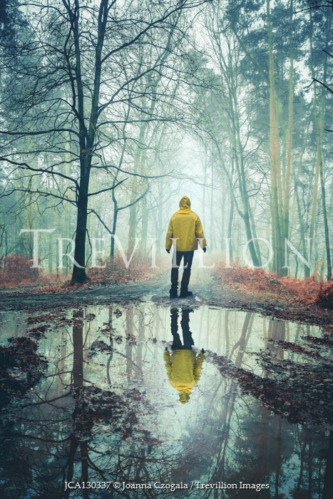 Joanna Czogala MAN WITH ANORAK REFLECTED IN PUDDLE IN COUNTRYSIDE Men
