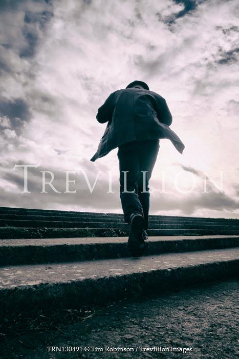 Tim Robinson Man walking on steps at sunset