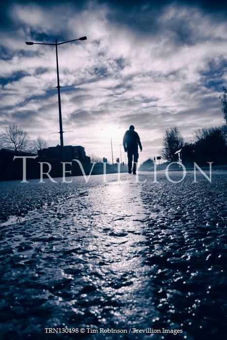 Tim Robinson Silhouette of man walking on road