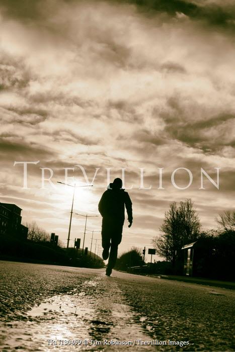 Tim Robinson Silhouette of man running on road