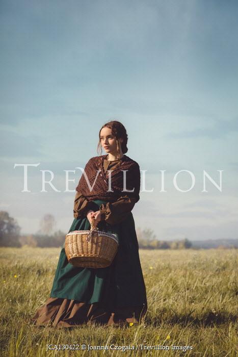 Joanna Czogala Young in Victorian dress holding basket in field