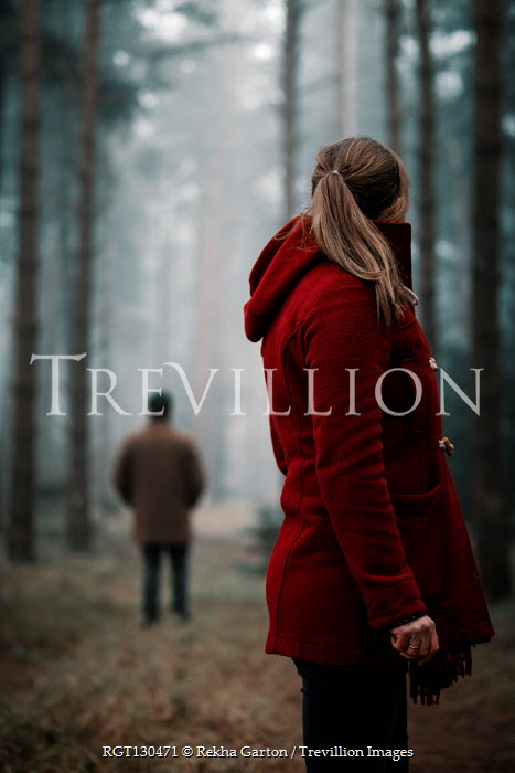 Rekha Garton Young woman in red coat with man standing in forest