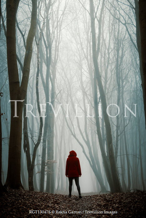 Rekha Garton Young woman in red coat standing in forest