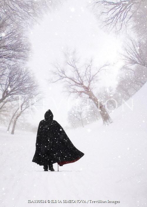ILINA SIMEONOVA Man in cloak walking on warped park path in snow