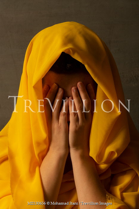 Mohamad Itani Young woman covering her face under yellow hood
