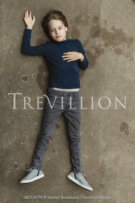 Shelley Richmond UNHAPPY BOY IN JEANS LYING ON GROUND Children