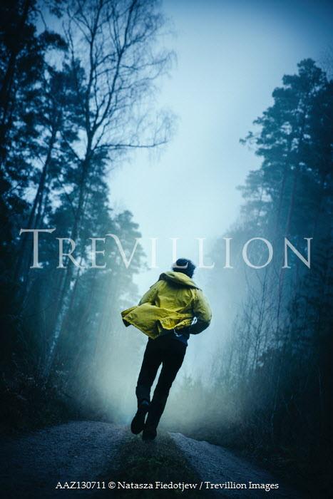Natasza Fiedotjew Young man in yellow raincoat running in woods