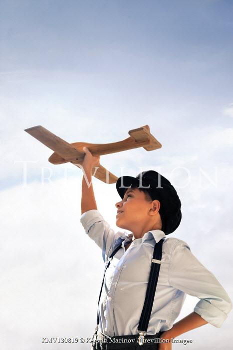Kerstin Marinov BOY WITH CAP HOLDING WOODEN AEROPLANE OUTDOORS Children