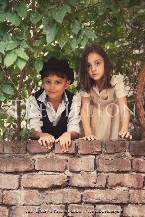 Kerstin Marinov GIRL AND BOY WATCHING FROM BEHIND GARDEN WALL Children