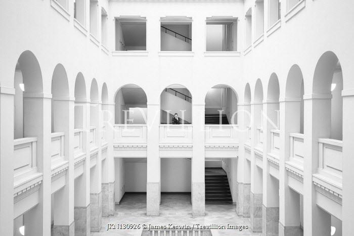 James Kerwin MAN ON BALCONY OF ATRIUM IN WHITE BUILDING Men