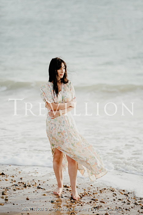 Angela Ward-Brown Young woman in floral dress standing on beach Women