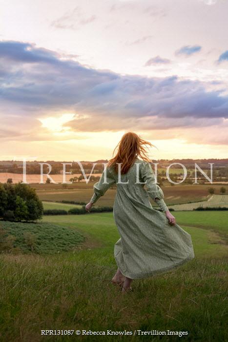 Rebecca Knowles Young woman in green dress walking in field