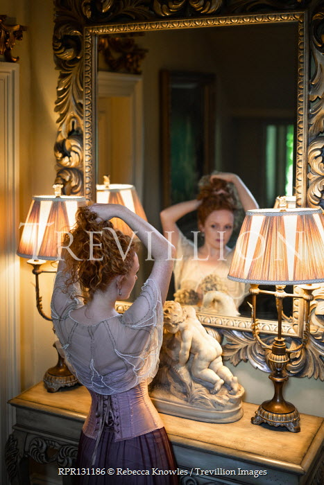 Rebecca Knowles Young woman adjusting hair in mirror
