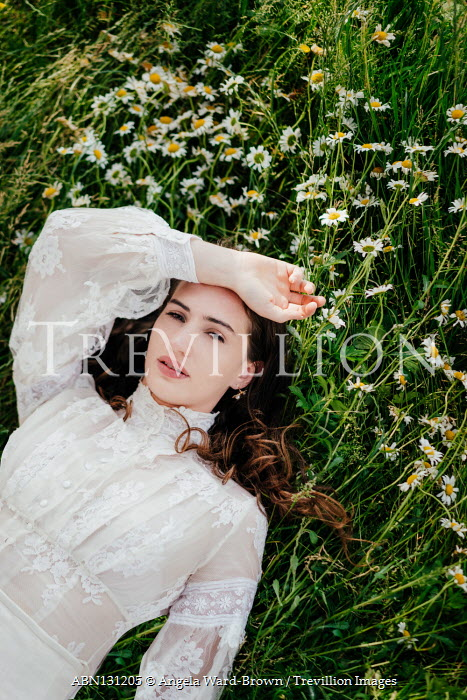Angela Ward-Brown Young woman in Victorian dress lying in daisies