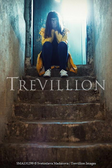 Svetoslava Madarova Young woman in yellow coat sitting on steps