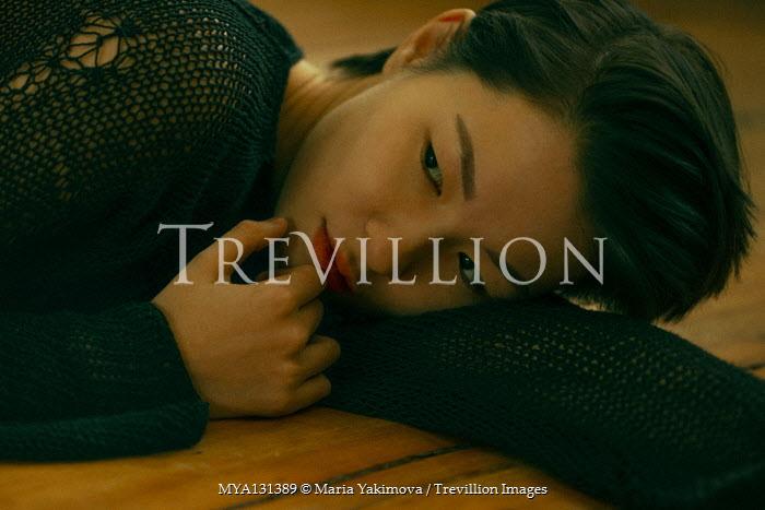 Maria Yakimova THOUGHTFUL YOUNG ASIAN WOMAN LYING ON FLOOR Women