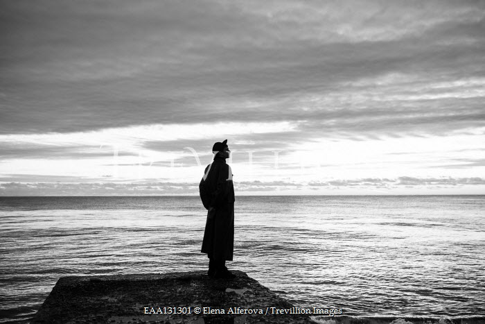 Elena Alferova SILHOUETTED MAN STANDING BY CALM SEA AT DUSK Men