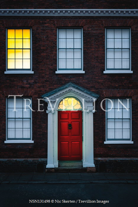 Nic Skerten Illuminated red door and lit window of house at night