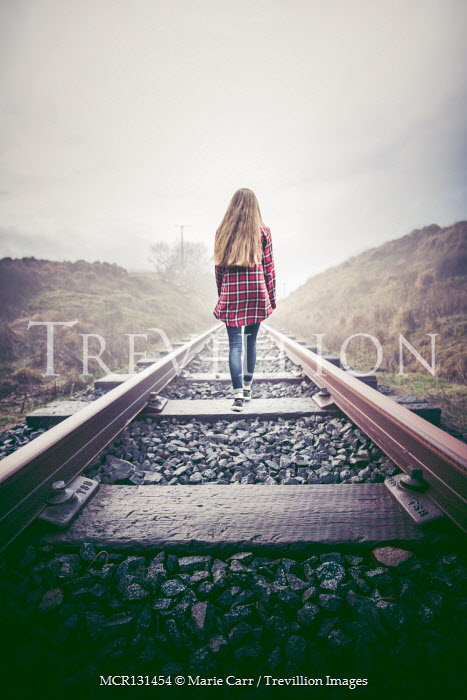 Marie Carr Young woman walking on train tracks