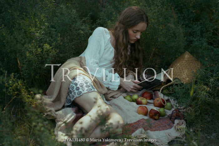 Maria Yakimova Young woman reading on picnic blanket