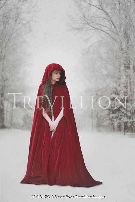 Susan Fox Young woman in red cloak in winter forest