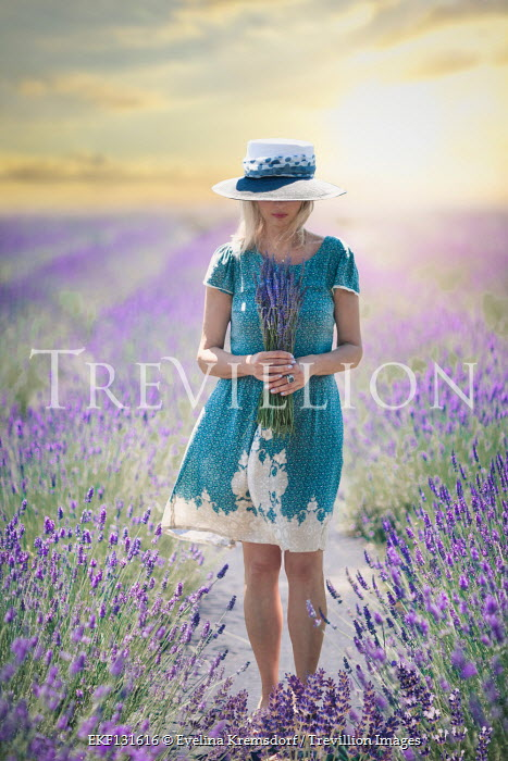 Evelina Kremsdorf Young woman in blue dress holding lavender in field