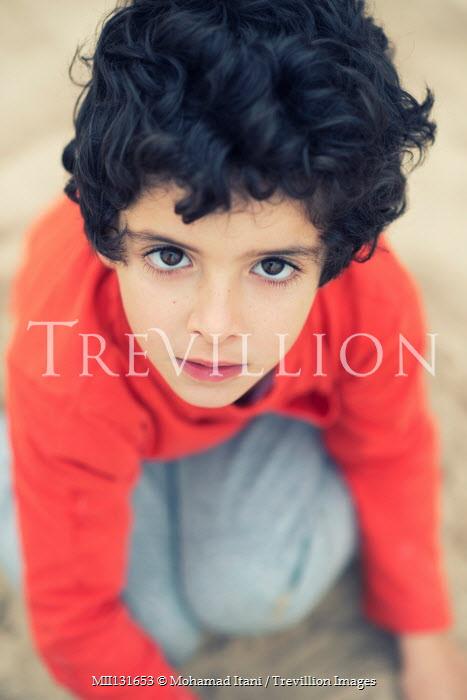 Mohamad Itani Boy crouching on beach