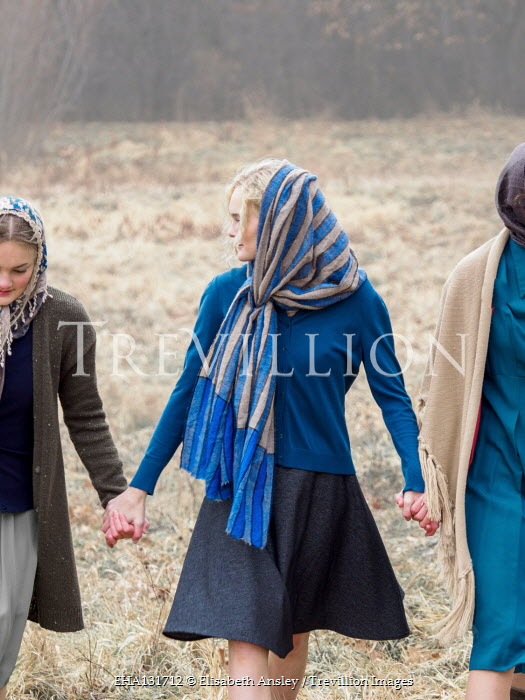 Elisabeth Ansley THREE RETRO WOMEN HOLDING HANDS IN FIELD Groups/Crowds