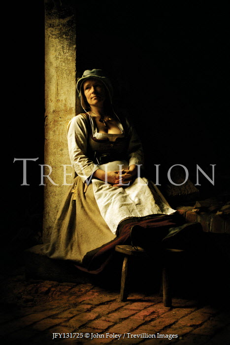 John Foley MEDIEVAL WOMAN SITTING IN SHADOW INDOORS Women